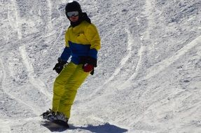 snowboarder in a yellow-blue suit on a snowy mountain
