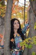 girl with long black hair among autumn trees