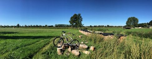 bicycle on stones among the green field