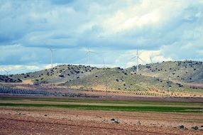 wind turbines on a hill above a field in spain
