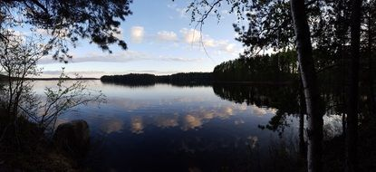 Evening sky mirroring on calm forest Lake, finland
