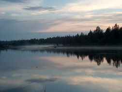 fog over forest lake in Finland