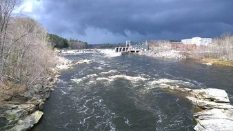 hydroelectric dam on Maine River at stormy winter weather
