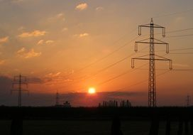 electric poles on the field at sunset background