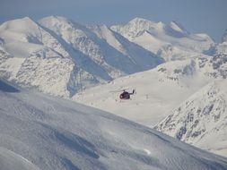 Helicopter flying over the beautiful snowy alps in Italy
