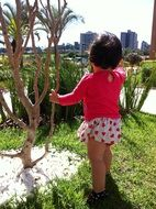 back view of Baby girl holding for branch at cityscape