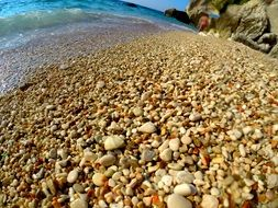 yellow round pebbles on the mediterranean coast in Italy