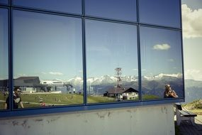 reflection of the picturesque mountain landscape in the mirror window of the house
