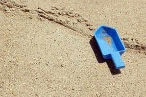 blue toy shovel in the sand