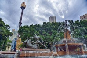 fountain and sculpture on square in cityscape with tv tower, australia, Sydney