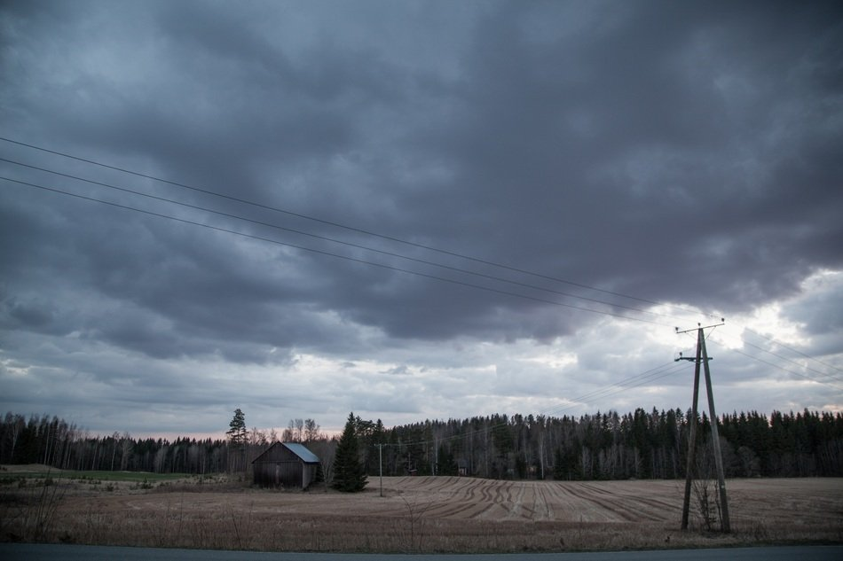 storm clouds over a shack in a field of finland
