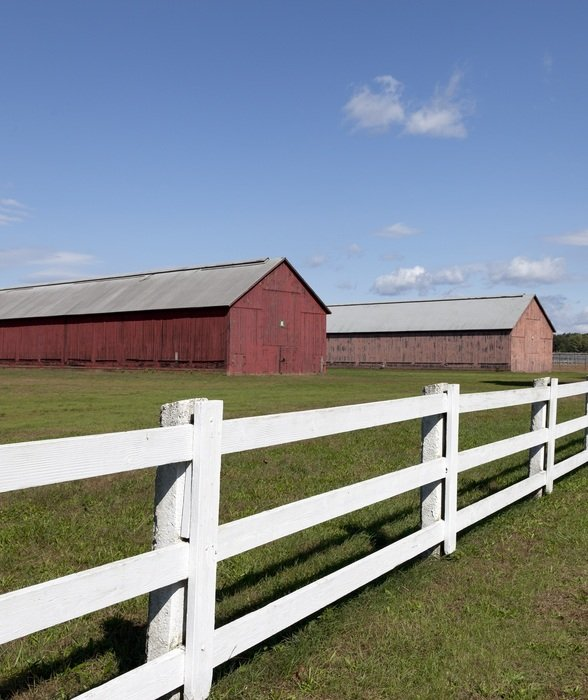 white wooden fence along large farm sheds on a sunny day