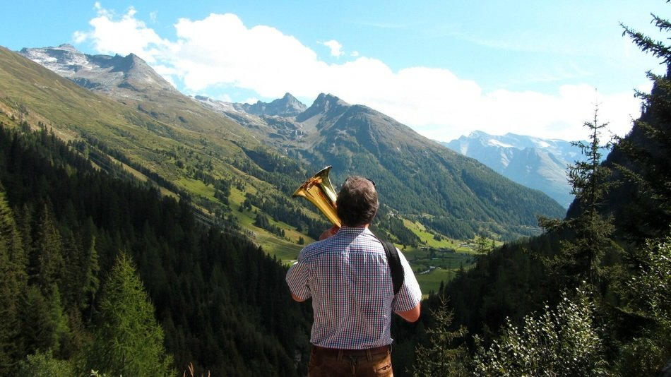 musician with wind instrument in the mountains of austria