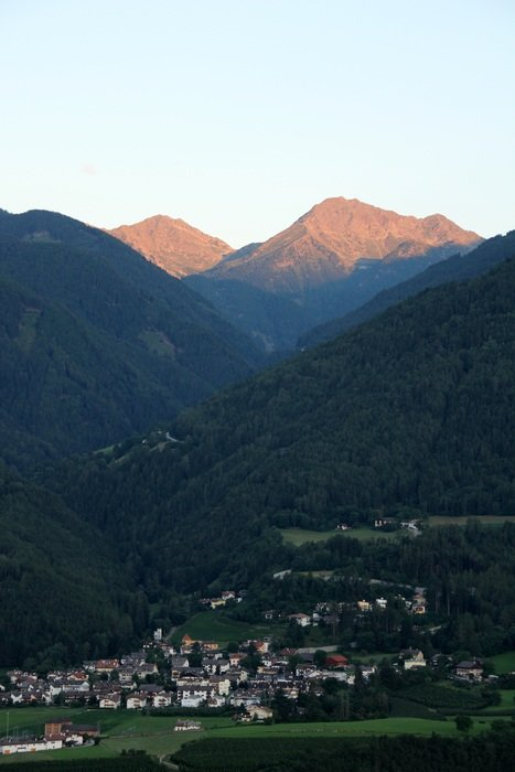 distant view of a village in the tyrol mountains at dusk