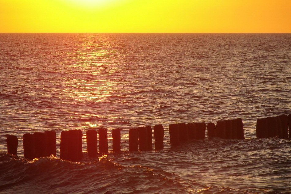 breakwater on the Baltic Sea in the rays of yellow sunset