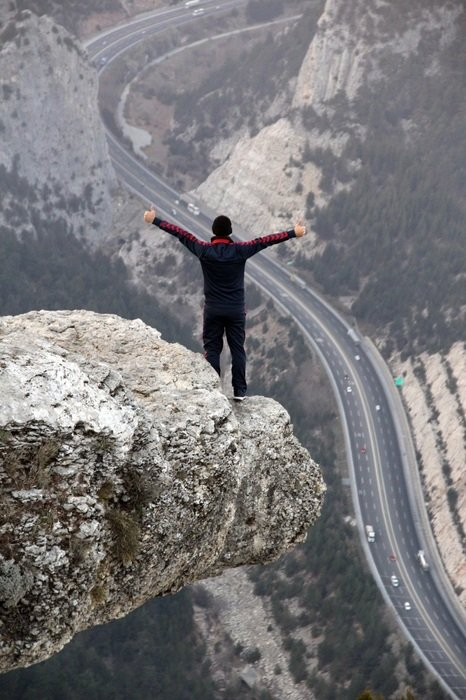 young man stands on Cliff above winding road, Freedom