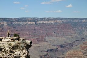 man on a cliff above the grand canyon