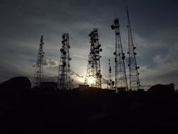 towers with antennas on the background of the evening sun