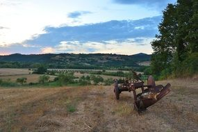 rusty machinery on a field on a hill
