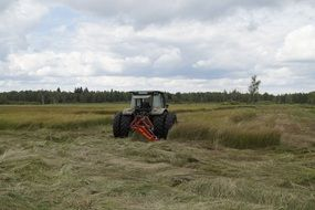 tractor mows grass among wetlands