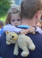 Child with toy teddy and Father