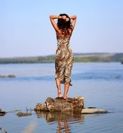 girl stands on a stone with her back