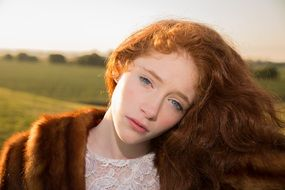 yound Girl with Red Hair and Blue Eyes in fur coat at Sunrise