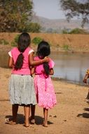 back view of two child girls standing together in front of water, India, Karnataka