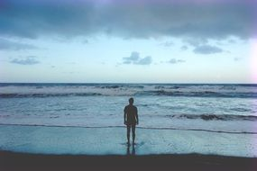lonely man standing on the beach