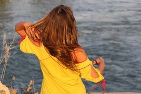 Tanned Girl in yellow dress at water, back view