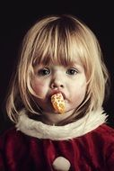 sad blonde child girl with Orange in mouth, portrait