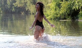 seductive brunette running in the water