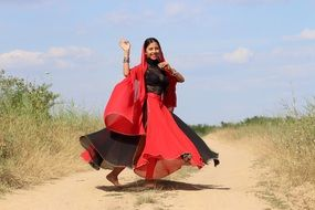 dancing Indian Girl in black and Red clothe on soil road