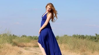 sensual girl in a long blue dress among nature on a sunny day