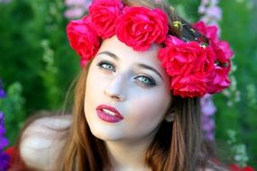 photo of a beautiful girl with a wreath of red roses on her head
