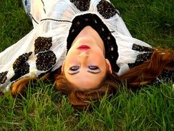 girl lying on her back on the grass