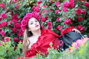 young woman posing on the rose bush background