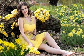 young woman in yellow dresses on the daffodils background