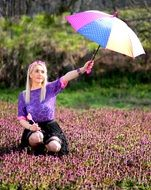 girl with a colorful umbrella in a flower meadow