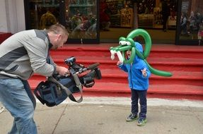 Child boy wearing Crocodile form Balloon posing in front of Camera