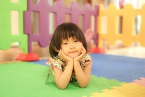 asian Child girl lays down on colorful floor
