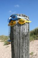 pacifier and swimming glasses on wooden pile on beach