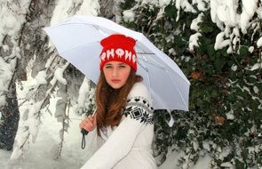 young woman in winter forest with umbrella