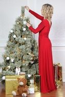 woman in red dress near christmas tree
