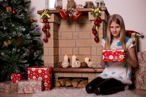 Christmas girl by the fireplace with gifts