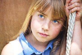 girl with blue eyes holds on to the rope
