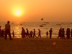 orange sky over the silhouettes of people on the beach in india