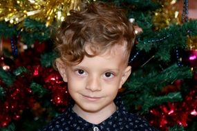 cute caucasian child Boy at Christmas Tree, head portrait