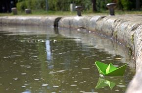 green paper boat on a pond in a park