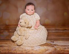 baby doll in a beige dress with teddy bear
